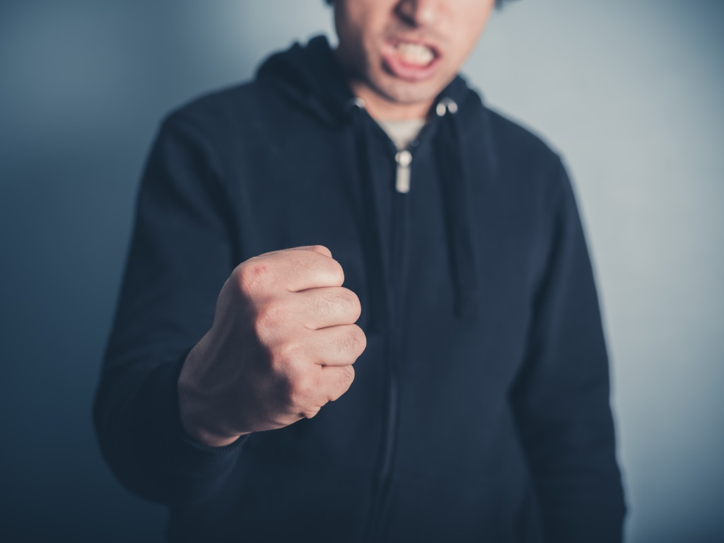 Close up on a young man raising his fist